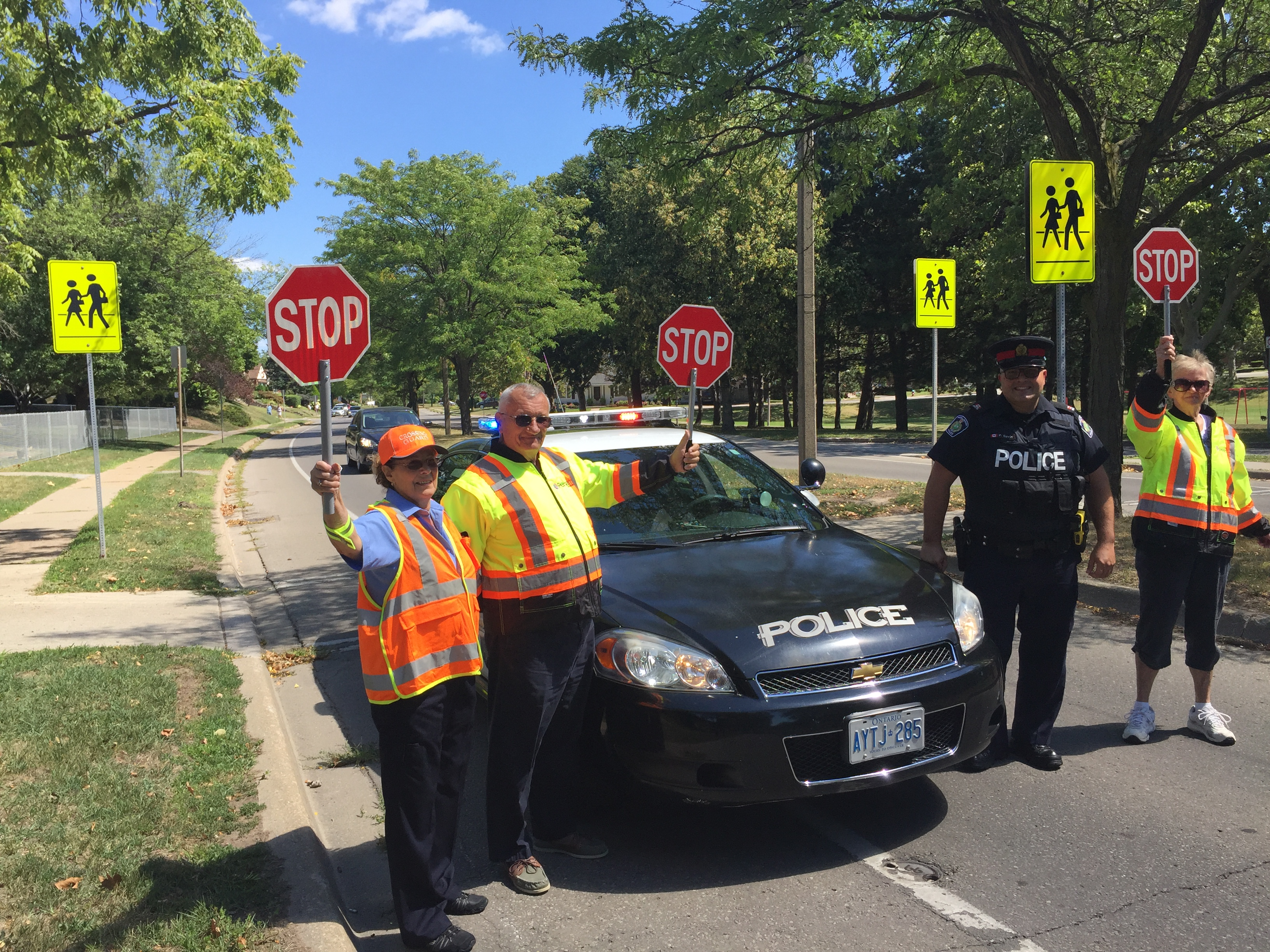 Officer and crossing guards working together