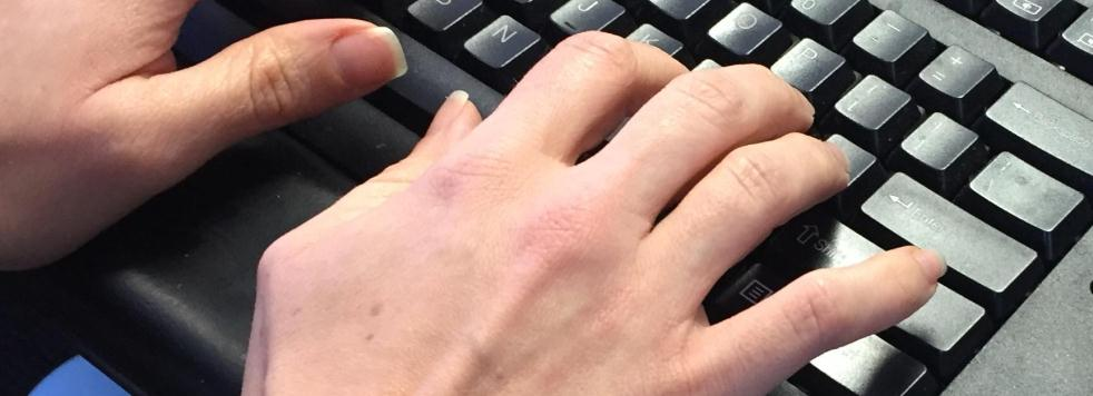 Hands typing at computer keyboard