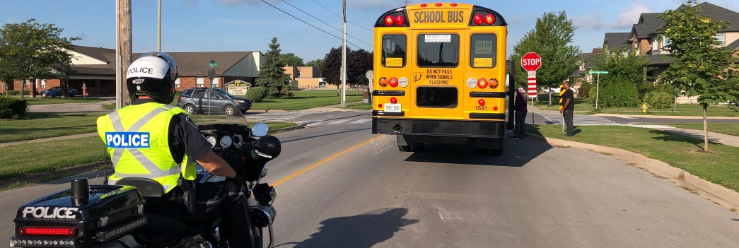 an officer on a motorcycle trailing behind a school bus